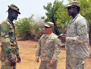 Army Spc. Lassana Traore, right, translates during a conversation between Army Pfc. Cody Anderson, center, and a Senegalese soldier during exercise Western Accord 14 at Camp Thies, Senegal, June 25, 2014. U.S. Army photo by Sgt. Takita Lawery