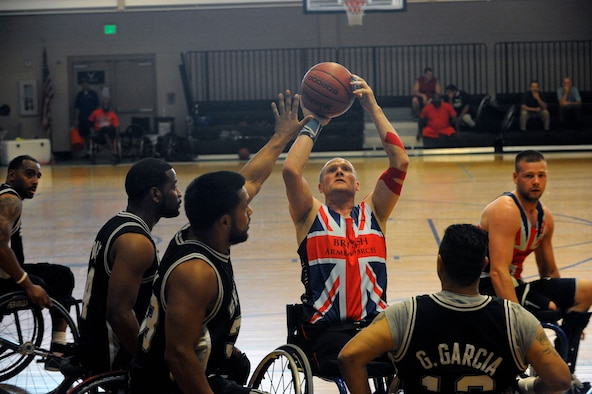 David Scott, center, shoots the basketball July 9, 2014, during 2014 Wounded Warrior Summer Invitational Adaptive Sports Tournament at the Rambler Fitness Center at Joint Base San Antonio-Randolph, Texas. The event features 100 wounded warriors from both the U.S. and the United Kingdom. (U.S. Air Force photo/Desiree N. Palacios)