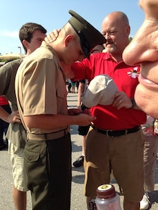 Private Daniel Pritchett, recent graduate of Bravo Company, 1st Battalion, admires a coin and ring given to him from his dad Kenneth Pritchett on June 20, 2014 at Marine Corps Recruit Depot Parris Island. Both son and father can now be called United States Marines.
