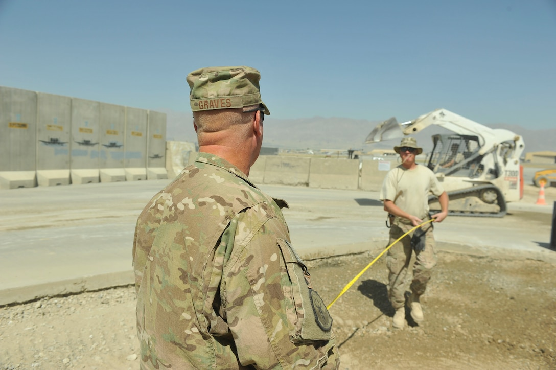 Master Sgt. Jeremiah Graves, left, and Master Sgt. Joshua Graves conduct measurements for a project July 1, 2014, on Bagram Airfield, Afghanistan. Joshua and Jeremiah, identical twins, are deployed from the Air National Guard's 148th Fighter Wing, Duluth, Minn. Jeremiah is a 455th Expeditionary Civil Engineer Squadron heavy equipment supervisor and Joshua is a 455th ECES project manager. (U.S. Air Force photo/Airman 1st Class Bobby Cummings)