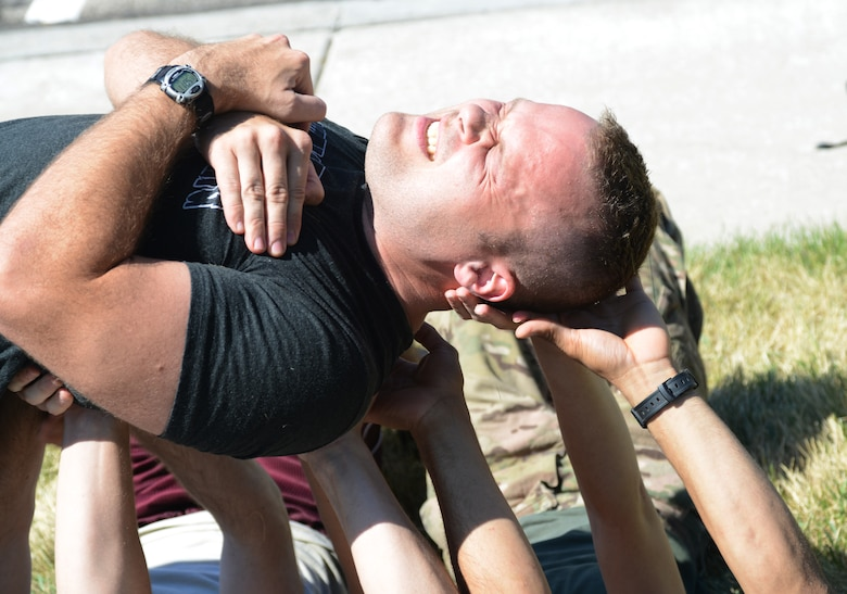 2nd Lt. Cameron White, 366th Comptroller Squadron financial services flight commander, grimaces while being carried across the hands of his fellow teammates July 12, 2014, at Mountain Home Air Force Base, Idaho. GORUCK challenges were developed by an Army Green Beret in an effort to offer elite, Special Forces training to participants. (U.S. Air Force photo by Senior Airman Benjamin Sutton/Released)