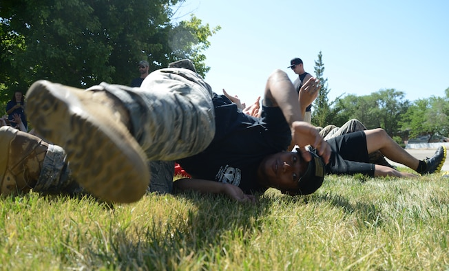 A person participating in the GORUCK Light Challenge July 12, 2014, slides off the bridge of hands which were supporting him at Mountain Home Air Force Base, Idaho. A key to the GORUCK Light challenge is how quickly participants are able to adapt to the obstacles and trust their teammates, for example when laying down on the arms of your team members and then being carried a big distance. (U.S. Air Force photo by Senior Airman Benjamin Sutton/Released)