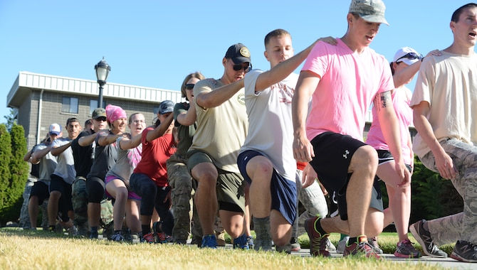 Members perform team lunges as part of the GORUCK Light Challenge July 12, 2014, at Mountain Home Air Force Base, Idaho. The new Air Force pilot program aims to get Airmen, dependents and Department of Defense employees involved in activities challenging them as a team and also encouraging a healthy, resilient lifestyle. (U.S. Air Force photo by Senior Airman Benjamin Sutton/Released)
