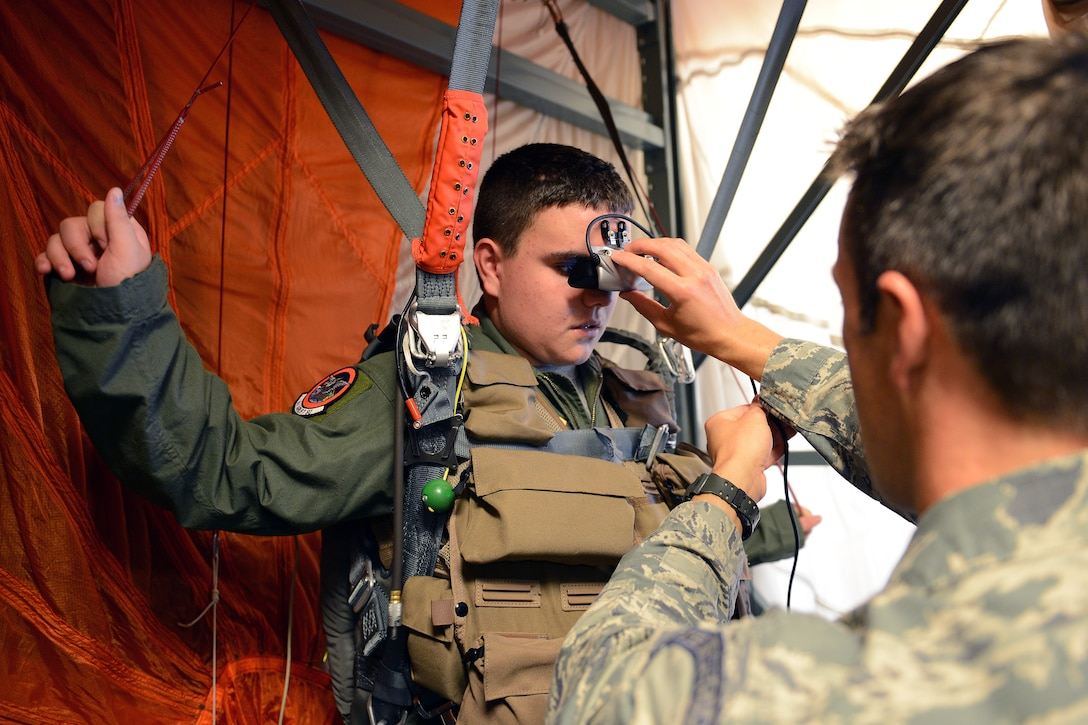 Jerry Connolly(left), pilot for a day, simulates controlling a parachute during a jump using a parachuting simulator under the supervision of Tech. Sgt. Logan Davis, 62nd Operations Support Squadron survival, evasion, resistance, and escape specialist, July 14, 2014, at Joint Base Lewis-McChord, Wash. Connolly simulated parachuting and landing on an aircraft carrier. (U.S. Air Force photo/Airman 1st Class Jacob Jimenez)