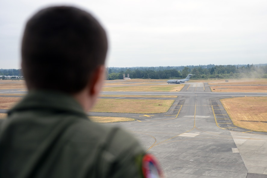 Jerry Connolly, pilot for a day, watches a C-17 Globemaster III perform a combat off-load from McChord Field's air traffic control tower July 14, 2014 at Joint Base Lewis-McChord, Wash. Connolly and his family were given a tour of the tower and briefed on tower operations. (U.S. Air Force photo/ Airman 1st Class Jacob Jimenez)