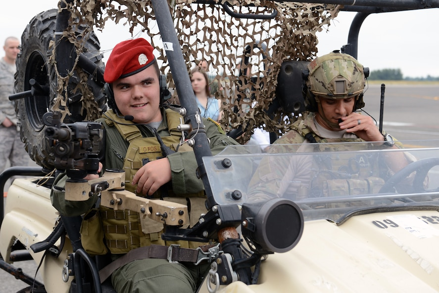 Jerry Connolly(left), pilot for a day, aims a machine gun while riding in an all-terrain vehicle driven by Senior Master Sgt. Mark Kistler, 22nd Special Tactics Squadron director of current operations, July 14, 2014, at Joint Base Lewis-McChord, Wash. Connolly has a rare inoperable brain cancer and was selected by the McChord Air Force Association to participate in the 4th Airlift Squadron's pilot for a day program. (U.S. Air Force photo/Airman 1st Class Jacob Jimenez)