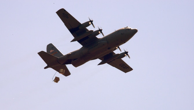 "Two container delivery systems are jettisoned out the back of a C-130H Hercules aircraft assigned to the 103rd Airlift Wing during an aerial drop training mission at the ""bean bag"" drop zone, Westover Air Reserve Base, Chicopee, Massachusetts, on July 12, 2014. The systems being released consist of four barrels filled with water weighing about 700 pounds and a high-velocity parachute tethered to the system allowing for safe descent to the ground. (Air National Guard photo by Tech. Sgt. Joshua Mead/Released)"