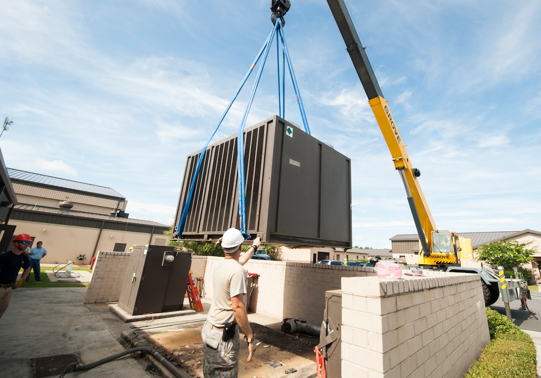 Civil engineer Airmen use a crane to remove an air-conditioning unit at Moody Air Force Base, Ga., July 14, 2014. The engineers replaced this unit after they determined a new one would cost less money in the long run than continually repairing the failing unit. (U.S. Air Force photo by Senior Airman Jarrod Grammel/Released)