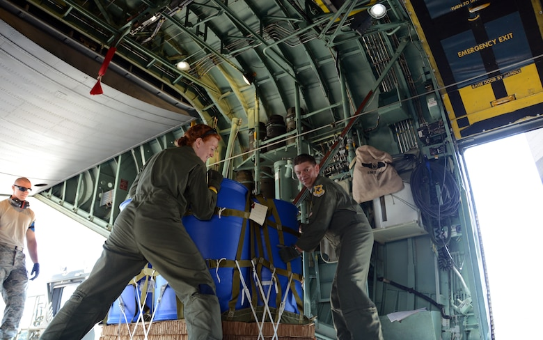 Senior Airman Kaitlin Cardello and Master Sgt. Joseph Amato shift a container delivery system into position on the floor rails of a C-130H Hercules aircraft during an air drop exercise at Bradley Air National Guard Base, East Granby, Connecticut on July 12, 2014. The exercise started with Airmen like Senior Airman Joseph Hamel (far left) loading the CDS onto a transport vehicle and transferring it onto the C-130H. From there, the loadmasters secure and position the load for air delivery. (Air National Guard Photo by Tech. Sgt. Joshua Mead/Released)