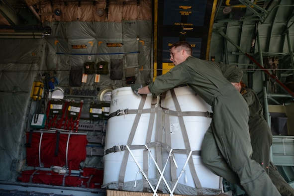 Staff Sgt. Danny Haynes and Senior Airman Kaitlin Cardello, both loadmasters with the 118th Airlift Squadron, push a container delivery system along the floor rails of a C-130H Hercules aircraft to get the load in position and secure for air delivery on July 12, 2014, at Bradley Air National Guard Base, East Granby, Connecticut. The aircraft was loaded with two sets of container delivery systems in preparation for multiple air deliveries while flying over Westover Air Reserve Base in Chicopee, Massachusetts. (Air National Guard photo by Tech. Sgt. Joshua Mead/Released)