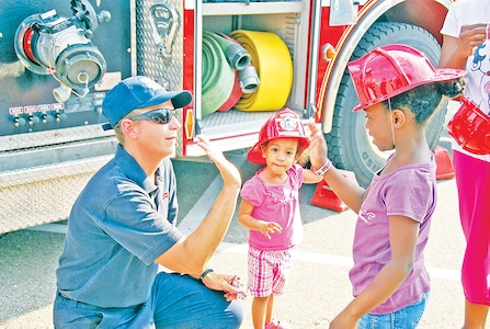 Tina Knowles, firefighter, FES, left, high-fives Nalaysia Raymond, right, as Nilannia Raymond, center, looks on during the 2013 National Night Out event. Fort Riley's 2014 National Night Out will be from 5 to 8:30 p.m. July 23 at Ware Elementary School.