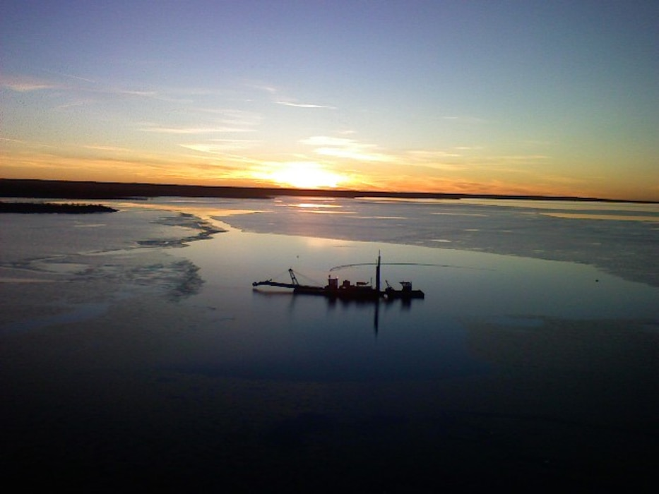 A tugboat, used during dredging operations at John Martin Dam & Reservoir in southeastern Colorado, sits on the water at sunset. Photo by Tony V. Urquidez, Nov. 24, 2008.