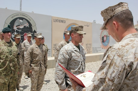U.S. Marine 1st Lt. Joshua Bridges, a native of Morganton, N.C., and assessments and plans officer, Regional Command (Southwest), stands at attention while Maj. Bob McCarthy, reads an award citation during a ceremony aboard Camp Leatherneck, Helmand province, Afghanistan, July 13, 2014. Bridges deployed to Helmand province during Jan. 2014 and was vital to RC(SW) planning efforts during the 2014 Afghan presidential elections and the upcoming transition of full security responsibility to the Afghan National Security Forces in the region by the end of 2014.