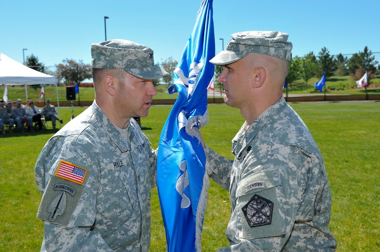 Col. Anthony Hale, 704th Military Intelligence Brigade commander, left, presents the 743rd Military intelligence Battalion guidon to Lt. Col. Andrew Pelka, 743rd MI Battalion commander, signifying his assumption of command June 19, 2014, at the softball fields on Buckley Air Force Base, Colo. During the ceremony, Pelka assumed command from Lt. Col. Gary Hausman after two years of service to the unit. (U.S. Air Force photo by Senior Airman Phillip Houk/Released)