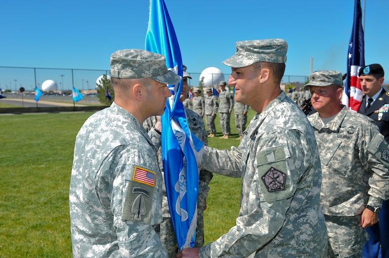 Col. Anthony Hale, 704th Military Intelligence Brigade commander, left, receives the 743rd Military Intelligence Battalion guidon from Lt. Col. Gary Hausman signifying his relinquishing of command June 19, 2014, at the softball fields on Buckley Air Force Base, Colo. During the ceremony Lt. Col. Andrew Pelka, 743rd MI Battalion commander, assumed command from Hausman after two years of service to the unit. (U.S. Air Force photo by Senior Airman Phillip Houk/Released)