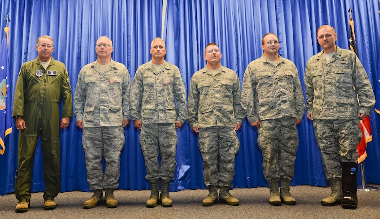 U.S. Air Force Maj. Gen. Thomas Moore, left, commander of the Georgia Air National Guard, and Lt. Col. Fred Walker, commander of the 202nd Engineering Installation Squadron (EIS), far right, pose with four members of the 202nd EIS after presenting them with Bronze Star medals during a Hometown Heroes Salute ceremony at Robins Air Force Base, Ga., July 13, 2014. Receiving the Bronze Star for meritorious service while deployed to Afghanistan in support of the global war on terrorism were; Maj. Will Jacobs, 2nd from left, Senior Master Sgts. Mark Buchanan and George Kight and Master Sgt. Jason Gardner.   (U.S. Air National Guard photo by Master Sgt. Roger Parsons/Released)