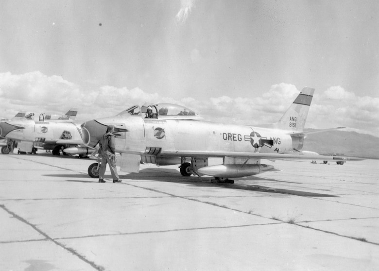 A fighter pilot prepares for a sortie in an OreANG F-86A Sabre jet fighter, serial number 48-151, of the 123nd Fighter-Interceptor Squadron during annual training at Gowen Field, Idaho, June 18,1954.  Note the distinctive Redhawk emblem on the fuselage below the cockpit.  The nose flash and stripe on the tail are colored green with black trim. (Courtesy 142FW History Archives)