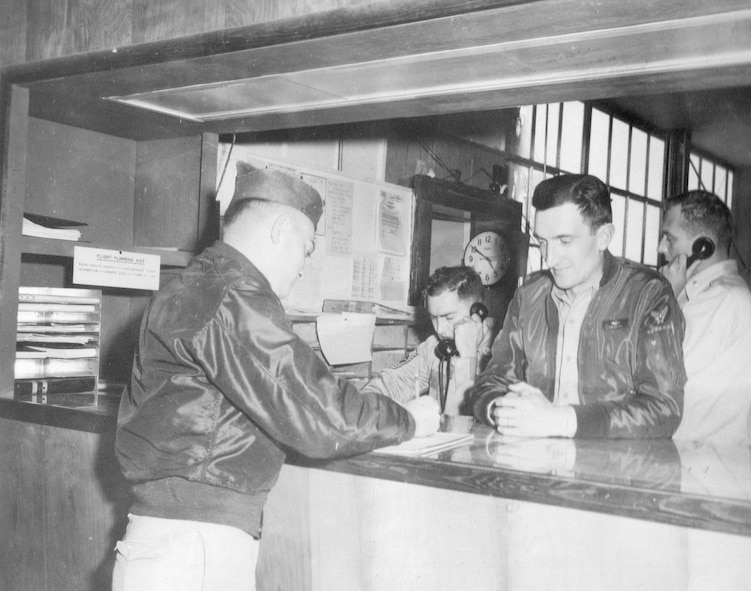 An unidentified aircrew member signs a document on the operations desk at Gowen Field, Idaho, as the Commander, 142nd Fighter-Interceptor Group, Lt. Col. Staryl C. Austin, Jr., looks on, June 18, 1954. (Courtesy 142FW History Archives)