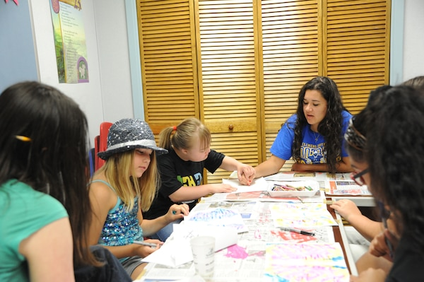 Kayla McKenney (right), Youth Program Staff volunteer, gives assistance to Juliette Gerst (left) and Alex Gerst in an art class July 9 during the Joint Base San Antonio 2014 Military & Family Readiness Arts and Dance Camp at JBSA-Randolph. (U.S. Air Force photo by Melissa Peterson)