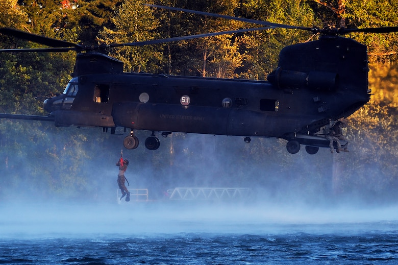 An Airman from the 22nd Special Tactics Squadron's Red Team is hoisted up to an MH-47 Chinook helicopter July 14, 2014, during helocast alternate insertion and extraction training with Soldiers from the 160th Special Operations Aviation Regiment at American Lake on Joint Base Lewis-McChord, Wash. The 22nd STS Airmen took part in joint operations with the 160th SOAR assisting their Soldiers in upgrade helocast and hoist training. (U.S. Air Force photo/Staff Sgt.Russ Jackson)