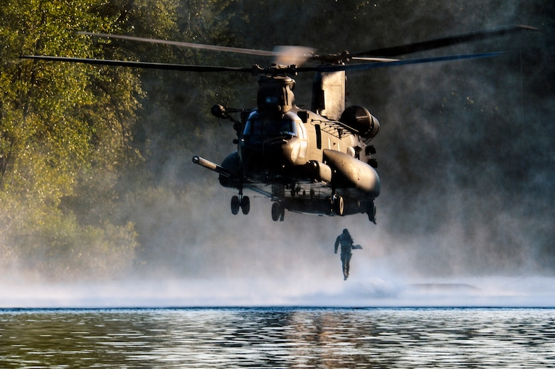 An Airman from the 22nd Special Tactics Squadron's Red Team jumps out of an MH-47 Chinook helicopter July 14, 2014, during helocast alternate insertion and extraction training with Soldiers from the 160th Special Operations Aviation Regiment at American Lake on Joint Base Lewis-McChord, Wash. Helocasting is an airborne technique used by special operations forces units for amphibious insertion into a military area of operation. (U.S. Air Force photo/Staff Sgt.Russ Jackson)