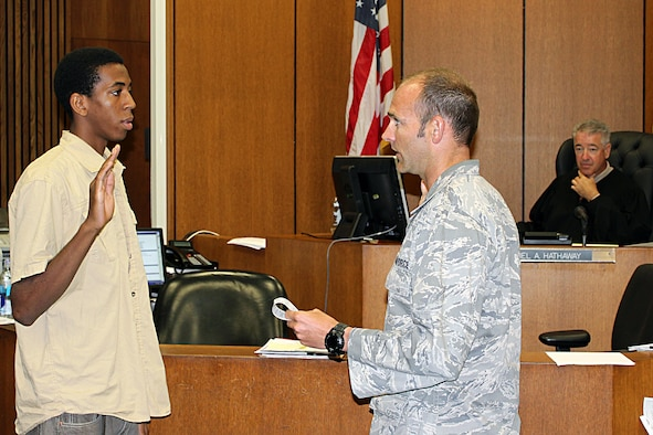 Torrey Gray is sworn in as a new recruit in the Michigan Air National Guard by 1st Lt. Robert McLean in the courtroom of Circuit Court Judge Daniel Hathaway in Detroit, July 15, 2014. Gray was sworn in at the court so that his mother, Tonya Gray, a Wayne County Sheriff's deputy who works at the court, could watch her son take the oath of office. Tonya Gray is also a member of the Michigan Army National Guard. McLean is the commander of the 107th Weather Flight at Selfridge Air National Guard Base, Mich., where Torrey Gray will serve as a member of the 127th Force Support Squadron. (U.S. Air National Guard photo by Tech. Sgt. Dan Heaton)