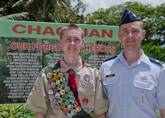 Troop 1420 Boy Scout Jackson Umlauf and his father Maj. Kurt Umlauf, 36th Munitions Squadron operations officer, stand in front of a memorial sign listing the names of the men lost in the Chagui'an Massacre in the village of Yigo, Guam, on July 14, 2014. The Umlaufs brought together the 36th MUNS and Boy Scouts of America Troop 1420 to update the forgotten memorial site. (U.S. Air Force photo by Senior Airman Katrina M. Brisbin/Released)
