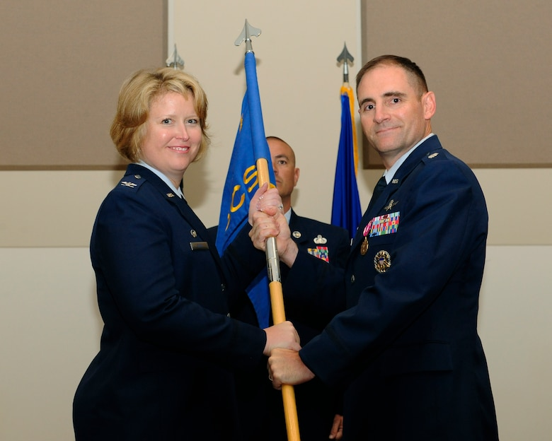Lt. Col. Hew Wells, right, relinquishes his command of the 460th Space Communications Squadron to Col. DeAnna Burt, 460th Operations Group commander, during the 460th SCS Change of Command ceremony July 17, 2014, at the Leadership Development Center on Buckley Air Force Base, Colo. The event signaled Maj. Christopher Kennedy, 460th SCS commander, assuming command from Wells, who served as commander of the 460th SCS for two years. (U.S. Air Force photo by Airman 1st Class Samantha Saulsbury/Released)