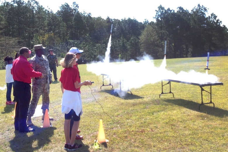 Senior Airman Manley McKinley (uniform, center), from the 169th Aircraft Maintenance Squadron, lends a hand during the model rocket launch phase of STARBASE's summer camp help at McEntire JNGB in June. (Photo courtesy of Mrs. Beth Barkley, STARBASE Swamp Fox)