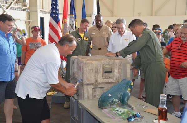 The HC-16 Bullfrogs' time capsule is opened inside a hangar at NASP's Forrest Sherman Field July 11. Squadron memorabilia from two decades ago was examined and will be re-interred with mementos of today. (Photo by Mike O'Connor)