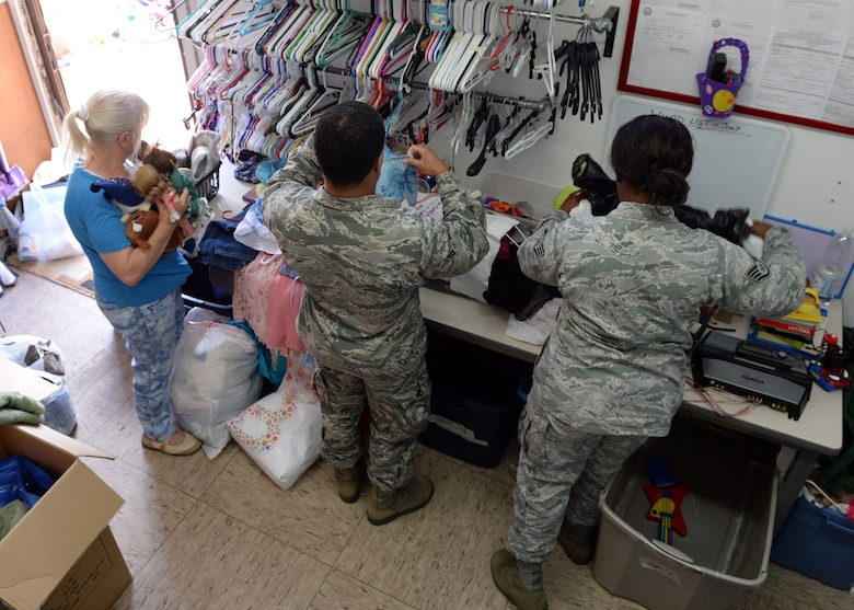 Herta Retterbush, Airman's Attic volunteer; U.S. Air Force Airman 1st Class Solomon Wright, 606th Air Control Squadron cyber operations technician from Havre de Grace, Md.; and Staff Sgt. Debonnae Cheeks, 606th ACS cyber operations technician from Melrose Park, Ill., sort clothes and other items in the staff room of the Airman's Attic July 15, 2014, at Spangdahlem Air Base, Germany. The staff comprises an all-volunteer force from both military and civilian occupations. (U.S. Air Force photo by Staff Sgt. Daryl Knee/Released)