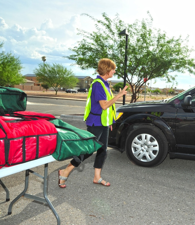 Mandy Petzer, Soaring Heights Communities receptionist, takes an order for two pizzas during the Drive-Thru Pizza Night held at the Welcome Home Center at Davis-Monthan Air Force Base, Ariz., July 16, 2014.  The discount pizza event is hosted by Soaring Heights on the third Thursday of each month.  (U.S. Air Force Photo by Airman 1st Class Chris Massey/Released)
