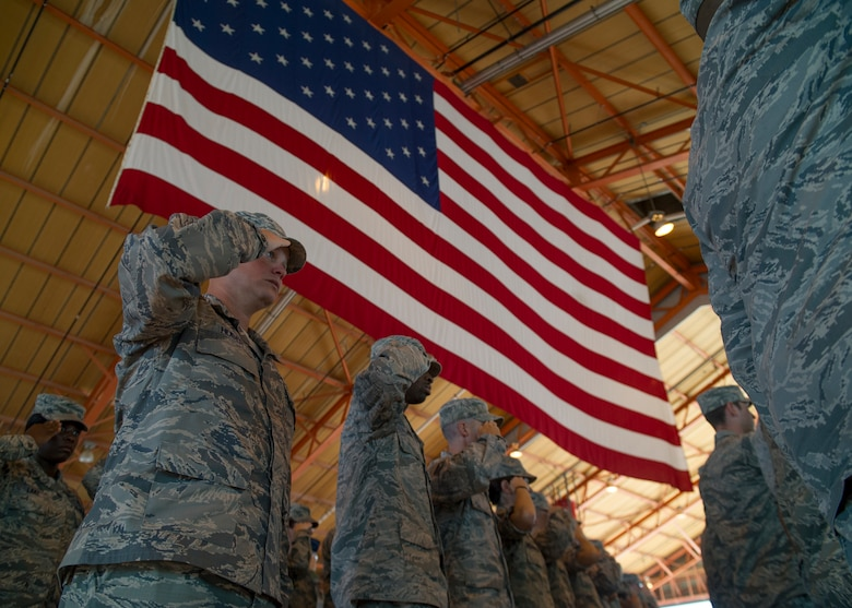 Airmen of the 49th Wing stand and salute the flag while the National Anthem plays during an assumption of command ceremony at Holloman Air Force Base, N.M., July 18. An assumption or change of command is a military tradition that represents a formal transfer of authority and responsibility for a unit from one commanding officer to another. (U.S. Air Force photo by Airman 1st Class Aaron Montoya / Released)