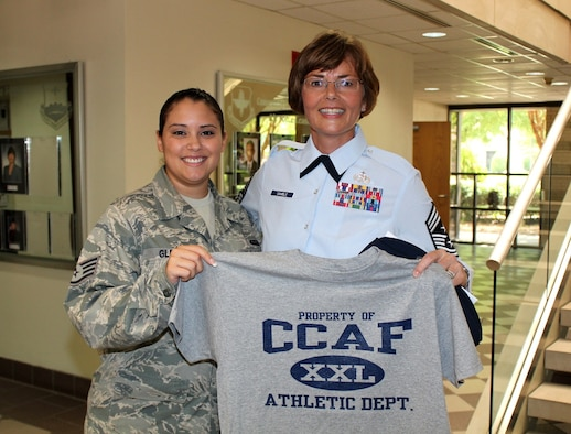 Staff Sgt. Vanessa Glenn, Community College of the Air Force, and Chief Master Sgt. Victoria Gamble, Air Mobility Command command chief, display their Community College of the Air Force T-shirt at Ryan Hall inside the CCAF Administrative Center at Maxwell Air Force Base, Alabama. The CCAF serves more than 305,000 active, Guard, and Reserve enlisted personnel, making it the world's largest community college system. (U.S. Air Force photo/Staff Sgt. Paul Davis)