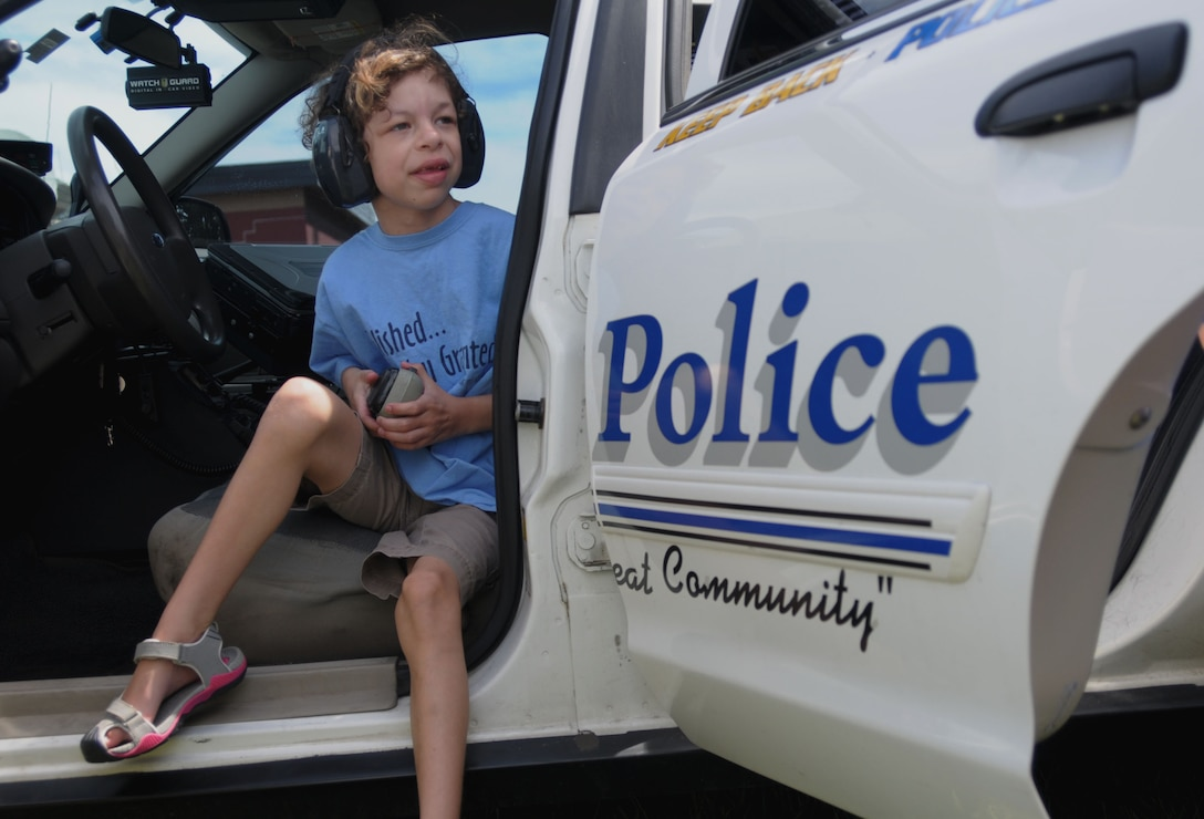 PEASE AIR NATIONAL GUARD BASE, N.H. -- Clare Rouillard experiences the inside of a police car after watching a demonstration from the Wells, Maine Police Department on how to operate the lights and speaker July 17. Eight children and their families were welcomed to Pease by Airmen who lined the sidewalk at the main gate, received demonstrations from the Dover Mounted Patrol and a Military Working Dog demonstration, enjoyed lunch at the Fire Department and toured the inside of a KC-135. (N.H. Air National Guard photo by Airman 1st Class Kayla McWalter/RELEASED)