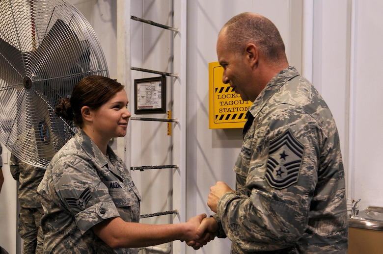 U.S. Air National Guard Command Chief Master Sgt. James W. Hotaling coins Senior Airman Micaelah Aleman, 144th Logistics Readiness Squadron logistics planner, during an all call held at the Fresno Air National Guard Base, Calif., July 13, 2014. Aleman was coined for her outstanding work she does in her unit and for the Wing as a whole.  (U.S. Air National Guard photo by Airman 1st Class Klynne Pearl Serrano/Released)
