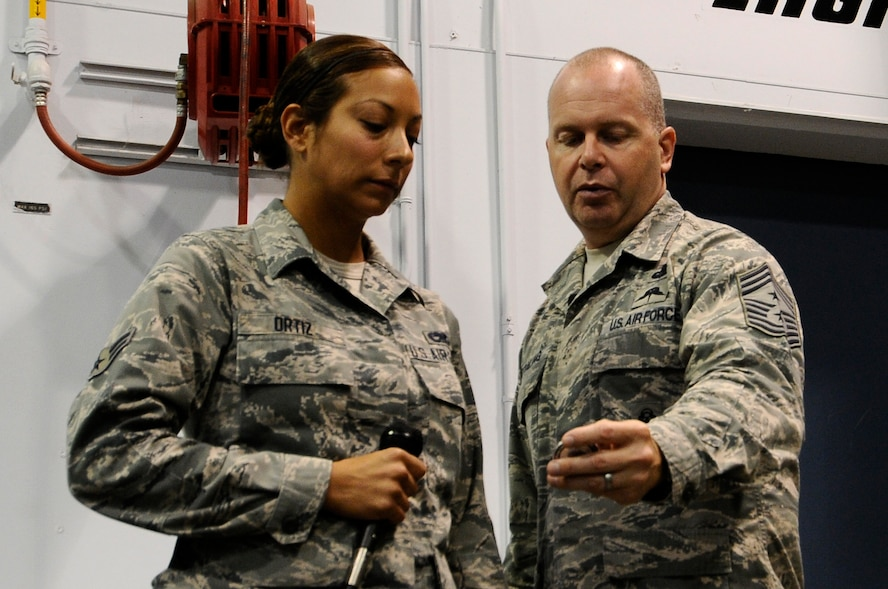 U.S. Air National Guard Command Chief Master Sgt. James W. Hotaling shows Airman 1st Class Amanda Ortiz, 144th Maintenance Group crew chief, his personalized Chief's Coin during an all call held at the Fresno Air National Guard Base, Calif., July 13, 2014. Ortiz was coined after she answered Chief Hotaling's three questions correctly.  (U.S. Air National Guard photo by Airman 1st Class Klynne Pearl Serrano/Released)