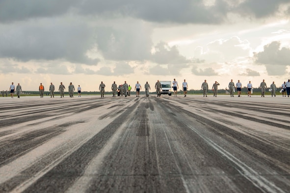 Members of the 482nd Fighter Wing line perform a foreign object damage walk as part of Wingman Day July 12, 2014, on Homestead Air Reserve Base, Fla. A FOD walk is conducted to remove potentially dangerous debris from the flightline and prevent damage to aircraft fuselage and engines. (U.S. Air Force photo/Senior Airman Jaimi L. Upthegrove)