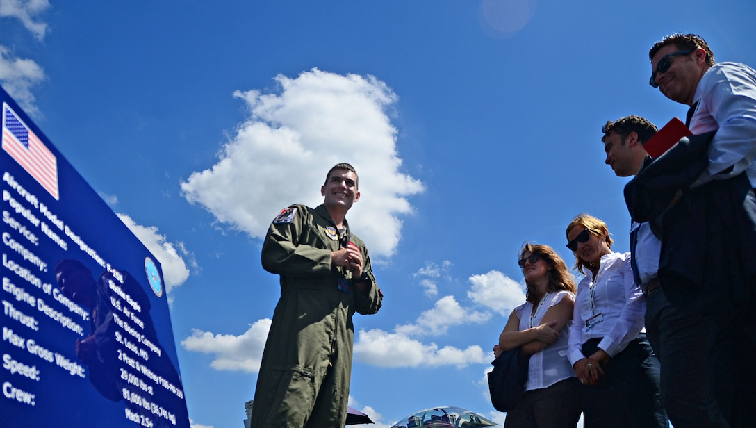 Capt. Tom Meyers, 494th Fighter Squadron F-15E Strike Eagle instructor pilot, discusses the aircraft's capabilities with spectators at Farnborough International Airshow, England, July 17, 2014. Public access was granted for spectators to ask questions and observe the aircraft up-close with pilots and aircrew members. (U.S. Air Force photo by Airman 1st Class Erin O'Shea/Released)