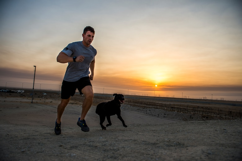 U.S Air Force Staff Sgt. Jesse Galvan, 386th Expeditionary Security Forces Squadron military working dog handler, runs in the early morning with his dog, Ritz, July 19, 2014 at an undisclosed location in Southwest Asia. Galvan has been partnered with Ritz for two and a half years and deployed twice with her. The Dallas-Ft. Worth native deployed here from Tinker Air Force Base, Oklahoma in support of Operation Enduring Freedom. (U.S. Air Force photo by Staff Sgt. Jeremy Bowcock)