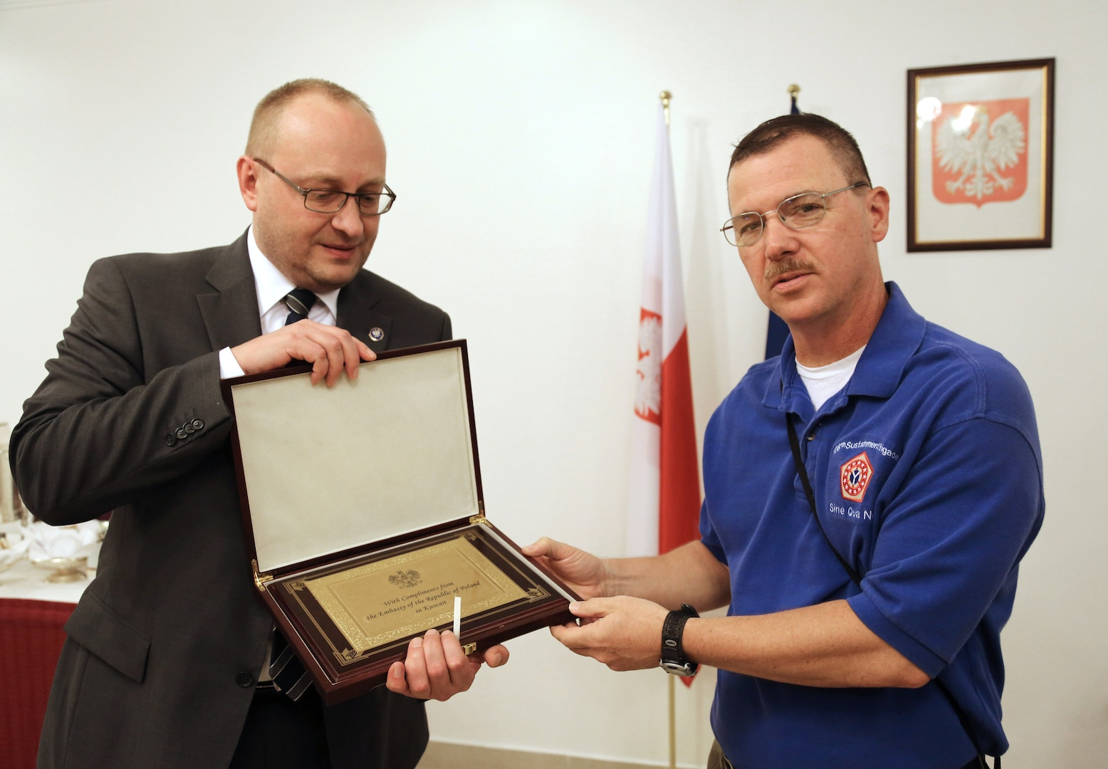 Grzegorz Olszak, Polish ambassador to the State of Kuwait and the Kingdom of Bahrain, left, presents a token of appreciation to Col. Drew Dukett, commander of the 108th Sustainment Brigade July 14, 2014, at the Polish Embassy of Kuwait.