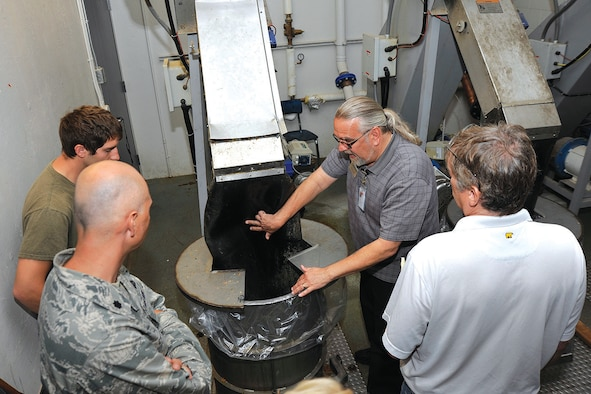 Glen Loyche shows Academy professors how dining hall food waste is converted into pulp at Mitchell Hall July 15, 2014, at the U.S. Air Force Academy, Colo. Loyche is the Mitchell Hall facility manager. (U.S. Air Force photo/Jason Gutierrez)