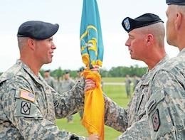"The 4th MEB, 1st Inf. Div. colors are passed from Col. Anthony ""Andy"" Munera to Command Sgt. Maj. Jon R. Stanley as Col. James F. Reckard III stands by during a change of command ceremony June 25 at Fort Leonard Wood, Mo. Munera assumed command of the brigade from Reckard. Stanley is the brigade's senior noncommissioned officer. Passing of the colors is symbolic of the responsibility and all other assumptions for the welfare and success of the unit passed from the outgoing to the incoming commander."