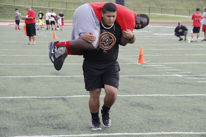 Naljay Pius, a Park Hill High School Trojans sophomore nose guard, fireman carries teammate junior Desmond A. Stirgus, a Trojans nose tackle, during the maneuver-under-fire portion of the Combat Fitness Test at the Trojans' football field July 20, 2014.