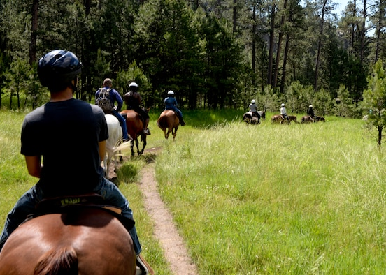 Ellsworth Airmen ride horses through Custer State Park, S.D., July 12, 2014, as part of an activity organized by the 28th Force Support Squadron outdoor recreation staff. The event, free for single Airmen, was designed to encourage participation in outdoor activities. (U.S. Air Force photo by Senior Airman Anania Tekurio/Released)
