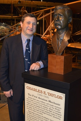 DAYTON, Ohio - Charles Taylor II, great-grandson of Charles E. Taylor, poses next to a bronze bust honoring his grandfather at the National Museum of the U.S. Air Force. Known as the first aviation mechanic, Charles E. Taylor designed and built the engine that made the Wright brothers' pioneering powered flights possible. (U.S. Air Force photo by Ken LaRock)