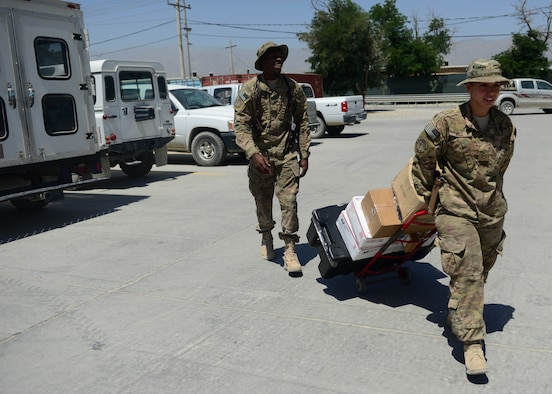 (From left) U.S. Air Force Senior Airmen Lorenza Kates and Victoria Hill, 455th Expeditionary Communications Squadron mail clerks deliver mail at Bagram Airfield, Afghanistan June 26, 2014.  Kates and Hill are responsible for handling mail for Airmen in the 455th Air Expeditionary Wing. They handle thousands of packages and letters per month.  Kates is deployed from Davis Monthan Air Force Base, Ariz. and a native of Dublin, Ga. Hill is deployed from Whiteman Air Force Base, Mo. and a native of Blanchard, La.  (U.S. Air Force photo by Staff Sgt. Evelyn Chavez)