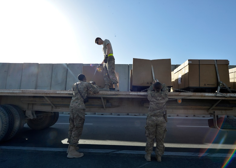 (From left) U.S. Air Force Senior Airman Lorenza Kates, 455th Expeditionary Communications Squadron mail clerk, Airman 1st Class Joshua Zehms, 455th Expeditionary Logistics Readiness Squadron vehicle operations and Senior Airman  Victoria Hill, 455 ECS mail clerk load a flatbed truck at Bagram Airfield, Afghanistan June 26, 2014.  Hill and Kates are responsible for delivering mail to Airmen assigned to the 455th Air Expeditionary Wing.  They average 77 pallets of mail per week that amounts to approximately to 38,500 pounds.  Kates is deployed from Davis Monthan Air Force Base, Ariz. and a native of Dublin, Ga. Zehms is deployed from Nellis Air Force Base, Nev. and a native of Pittsburgh, Pa.  Hill is deployed from Whiteman Air Force Base, Mo. and a native of Blanchard, La. (U.S. Air Force photo by Staff Sgt. Evelyn Chavez/Released)