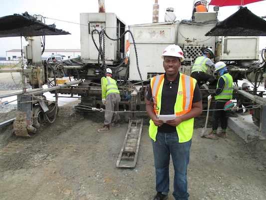 Tony Morgan, advancing minorities in engineering program intern, observes a slip form paver, used to separate and smooth out wet concrete until it dries into place, at U.S. Army Garrison Humphreys.