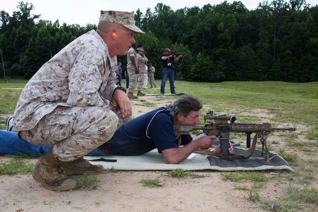 Staff Sgt. Nicholas Carson, a small arms weapons instructor, watches as William Goggins, attorney with Goggins Law Firm from Mattituck, N.Y., fires a weapon aboard Marine Corps Base Quantico on July 18, 2014. Seventeen civilian leaders from around the country attended the forum which is held five times a year.
